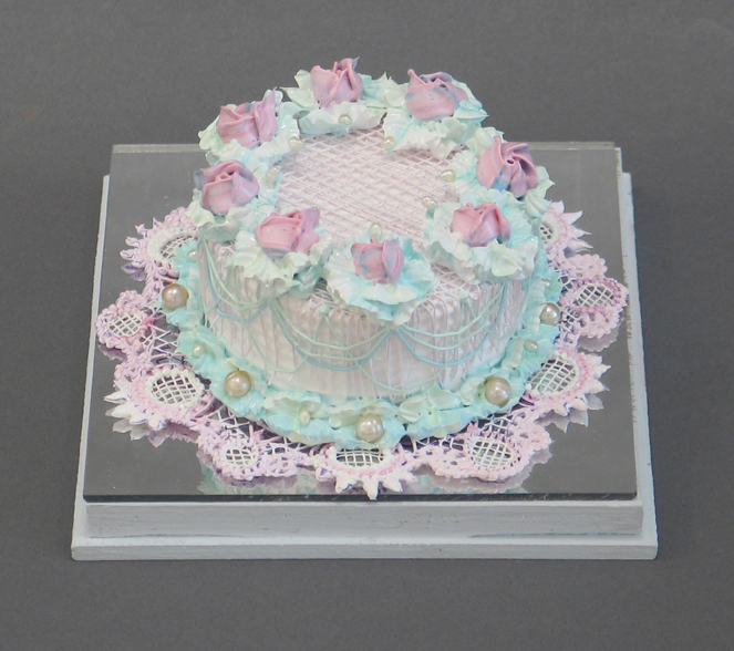 Acrylic pink cake with pink flowers on top and pearls