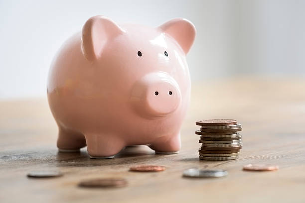 Loose coins and a stack of coins are lying on a wooden table in front of a pink ceramic piggy bank. The selective focus is on the piggy banks face. The coins are bronze and silver and are to be deposited into the piggy bank as savings.
