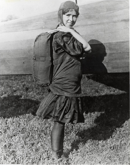 Tiny Broadwick posed beside a plane in flying gear, with parachute, circa 1912. Via the Smithsonian National Air and Space Museum.