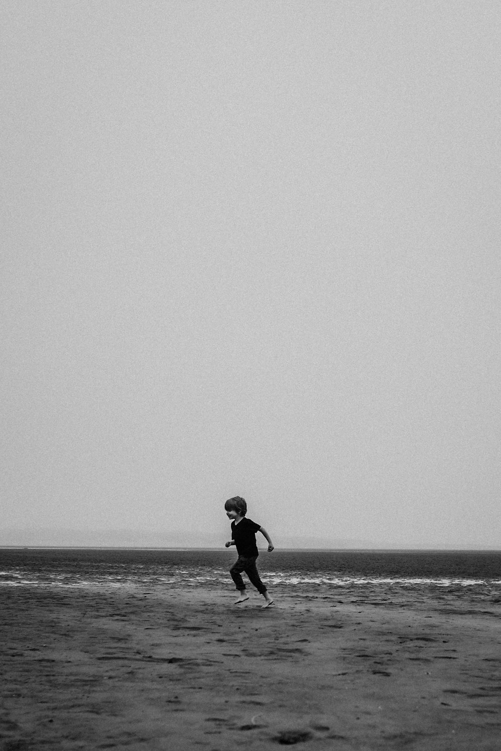 Boy running on beach in Lincoln City Oregon