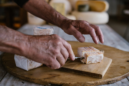 Our-Story-richard-cutting-washed-rind-pink-and-white-terrace-cheese.jpg