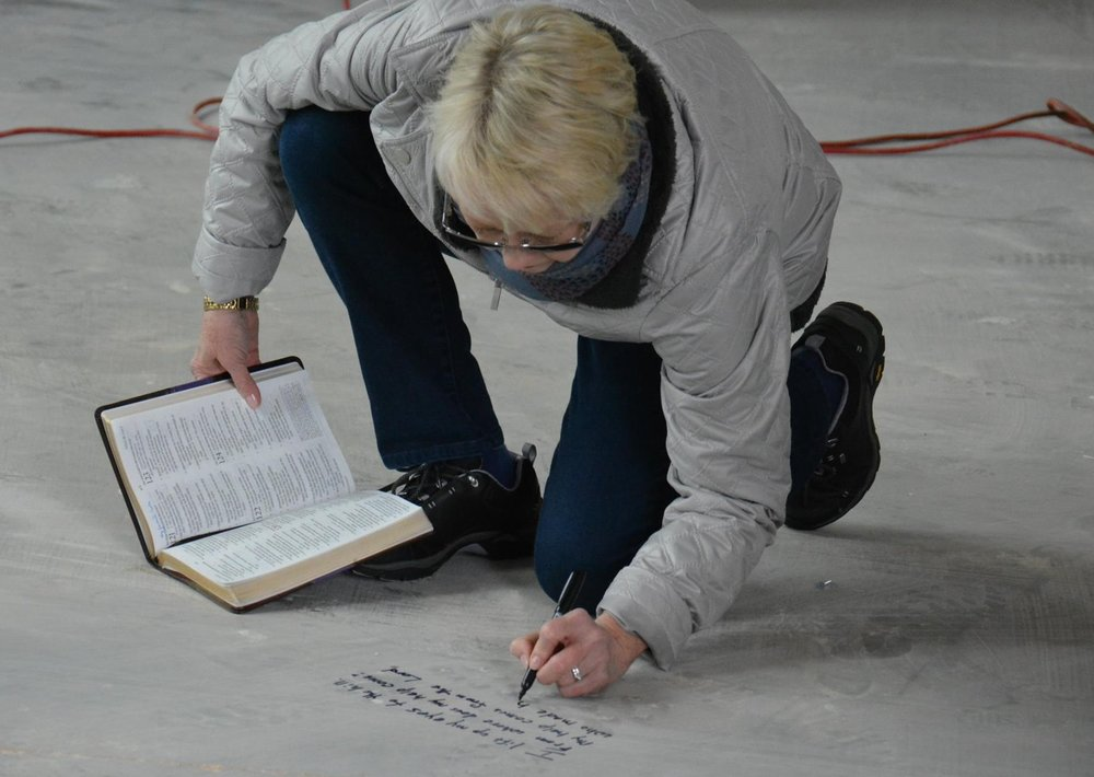 Parishoners wrote Bible verses on the concrete before flooring was installed.