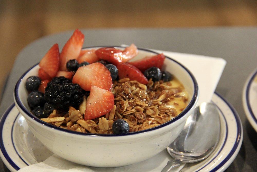 Yogurt topped with fresh fruit, honey, and granola