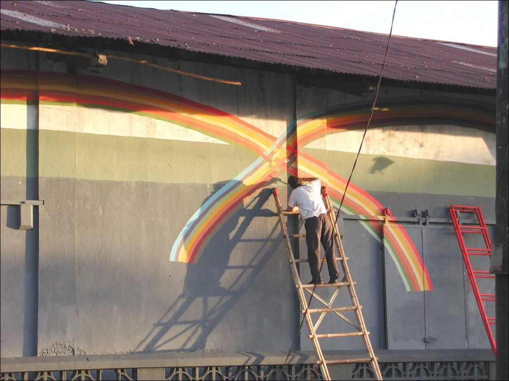 Alicia on a ladder, working on a public art installation in Indonesia