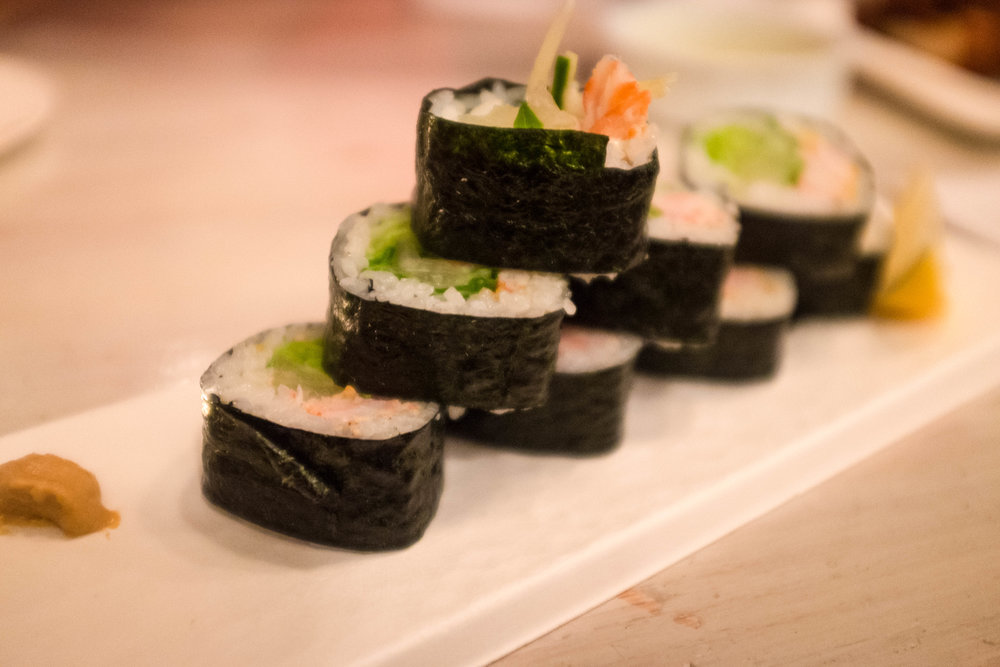 A shrimp and avocado sushi roll for the pescatarian of the group. It is sitting on top of a biodegrable serving platter.