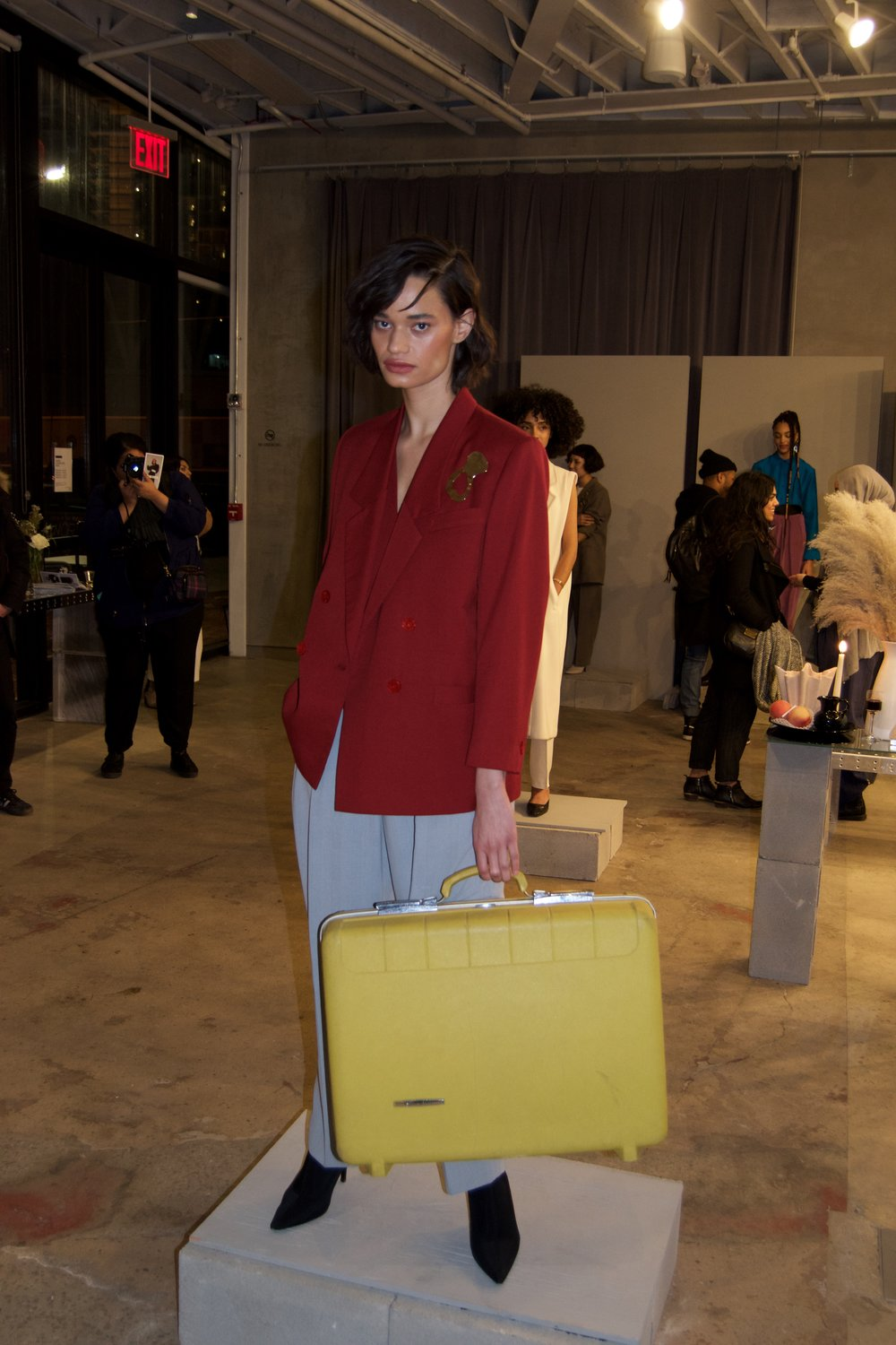 Tierra, holding a cute vintage yellow suitcase modeling all pieces from The Break.