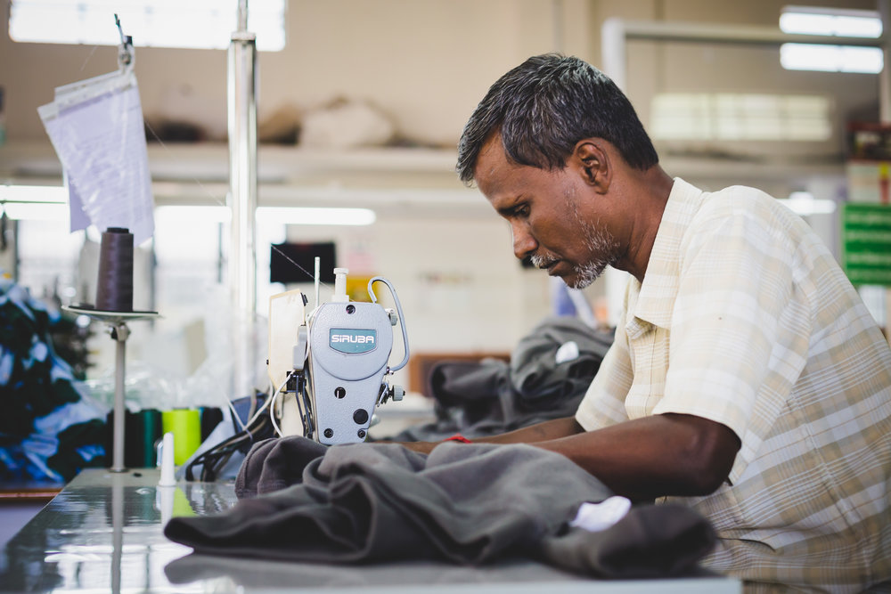 A member of the Mila family, KTO's main manufacturer in India, works intently on a clothing piece.
