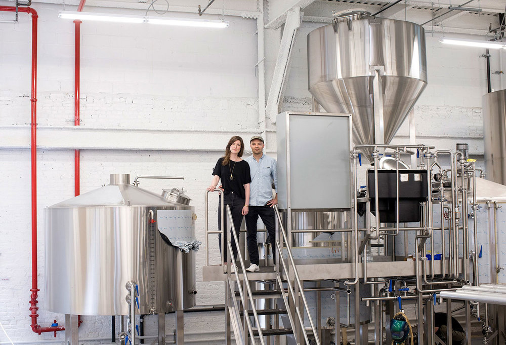 Image: Joe and Lauren Grimm, spouses and founders of Grimm Artisanal Ales, with their new brewing equipment at the brewery and taproom in Williamsburg, Brooklyn, which they hope to open in September. Credit Brian Harkin for The New York Times