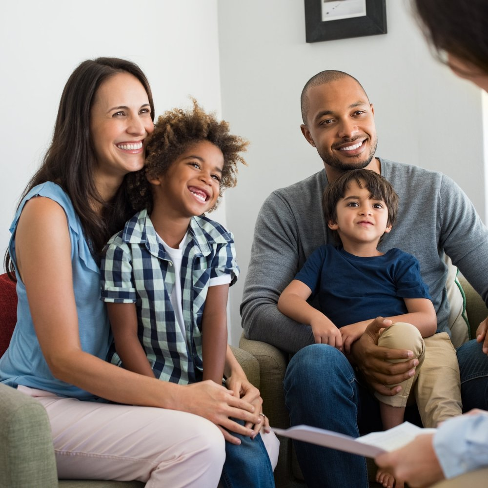 2_ShSt_Adoption_stock-photo-happy-young-family-sitting-on-couch-and-talking-with-family-counselor-smiling-parents-with-adopted-663456385.jpg