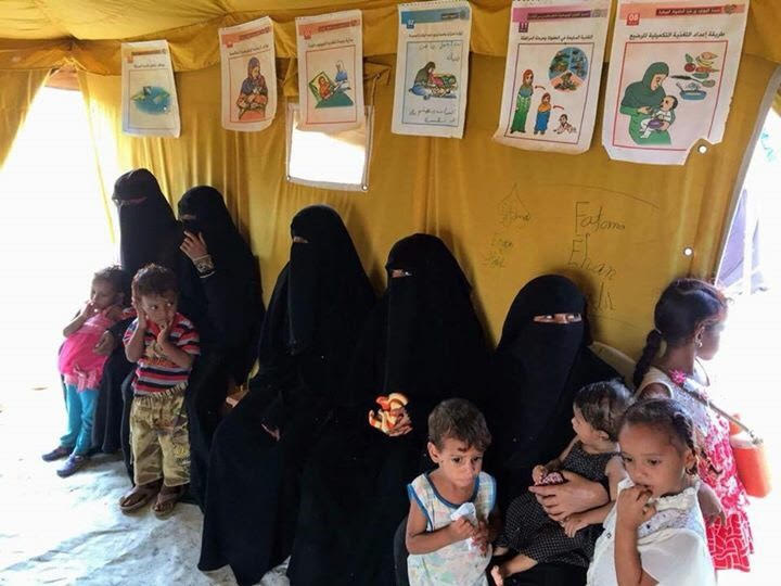 Yemeni refugee women and children in the Markazi camp's nutrition tent, which runs a blanket feeding program for children ages 6 months to 5 years and pregnant and lactating women. It also provides vitamin supplements and promotes the importance of exclusive breastfeeding for up to six months with adequate supplementary feeding.