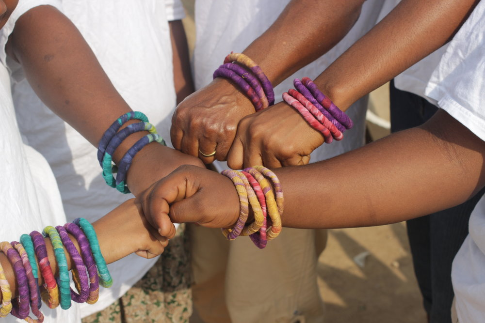 Close-Up of Workers and Family Modeling MFC Bracelets