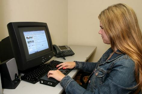 Young vision-impaired woman using a computer with assistive technology.