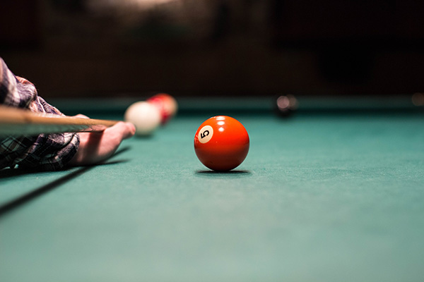 A billiard player shooting a ball. The aim and skill is like what it takes to work on your local SEO if your aim is to win with your website SEO for local listings.