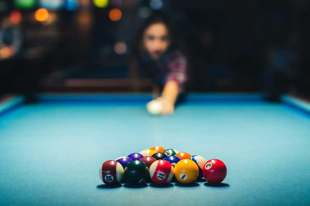 Woman at a pool table, taking aim at the balls.