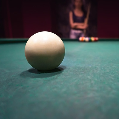 A white billiard ball on a table with a woman in the background, ready to shoot the ball.