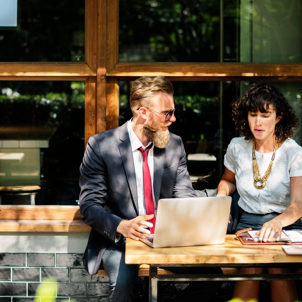 A man and woman sitting outside a cafe in discussion, looking at a laptop.