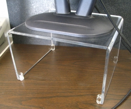 "Flat Screen Monitor Riser   Item #  MR-1060  Price:  $25.70 each  Dimensions:  10.00"" W x 6.00"" H x 8.00"" D Dim. O.D. Our monitor risers can help stop neck strain. Constructed from 1/4"" clear acrylic. Unit shown is 6.00"" tall. Designed with clear non-skid feet at the base edges. Polished edges. Custom sizes available."
