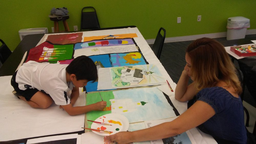 Mom and son painting canvas together.