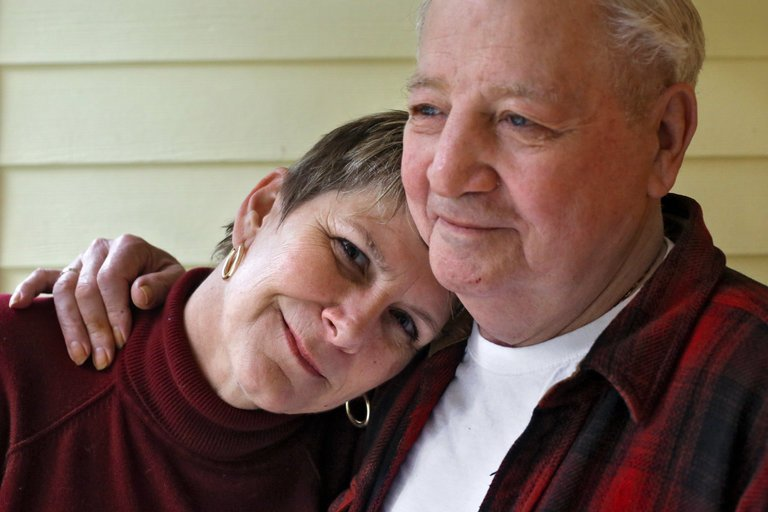 Gina Rinehart, left, poses for a portrait with her father at his home near Hoodsport, Wash., on March 3, 2017. Bub Hall has lung cancer and Ms. Rinehart has been helping take care of him for four years. Credit: David Ryder for The New York Times