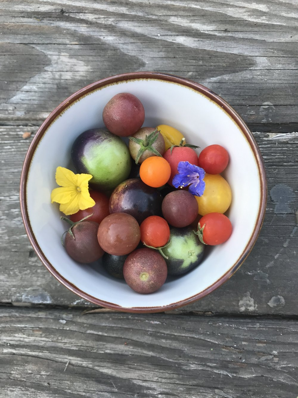 Tomatoes and edible flowers in a ceramic bowl