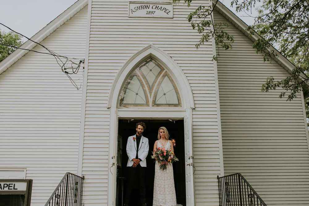 Birde and groom stand at door of old church in Iowa, with vintage window above them and vintage style wedding dress, holding pink and cream bouquet