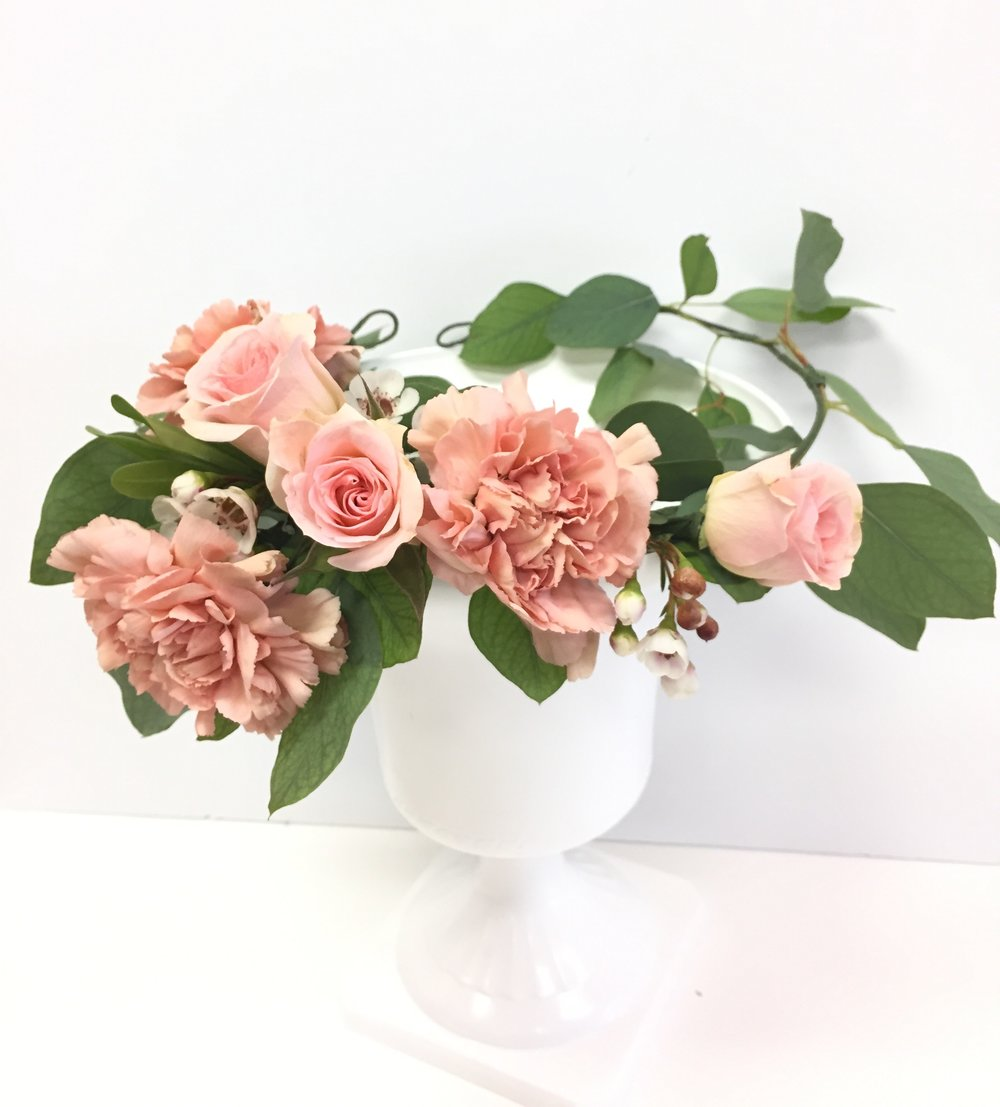 'Classic Crown': Spray roses and a larger type of flower, on an adjustable base of greenery.