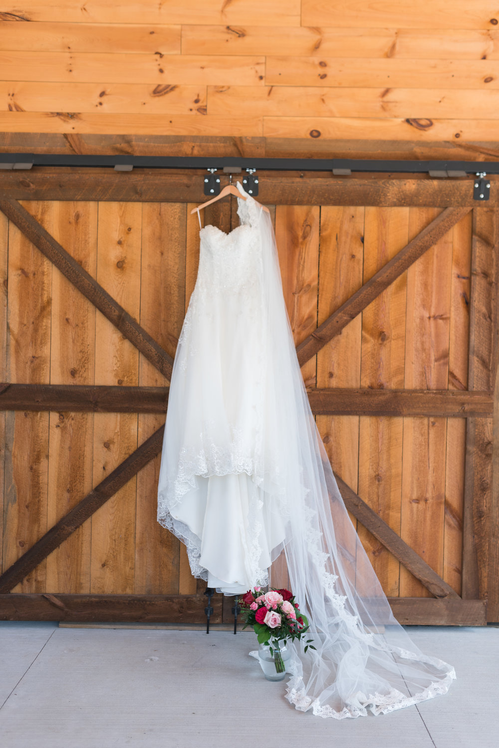 wedding dress, long veil, and wedding flowers in glass vase in front of barn door in Des Moines iowa