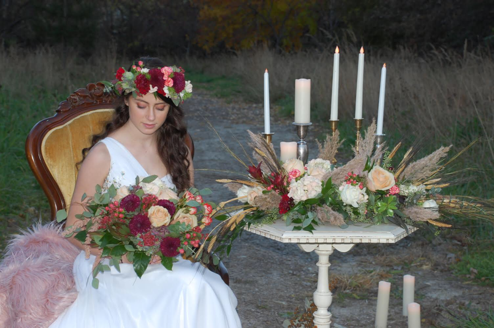 bride wears boho floral crown in reds and pinks, sitting by candles with flower arrangement by Lavender Blue with red, creams, blushes, and some dried fall grasses, rests on white vintage table