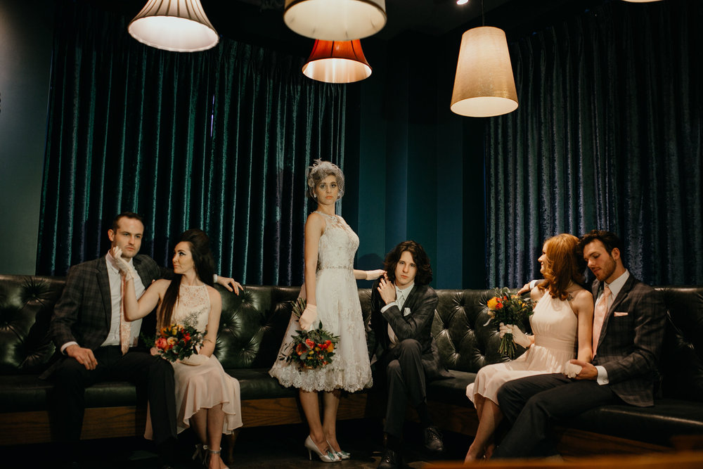 Retro wedding style at Hello Marjorie in Des Moines Iowa, with vintage gloves and jewelry, vintage hat worn by bride, bridal party sits together on long leather couch and bride wears a short retro wedding dress