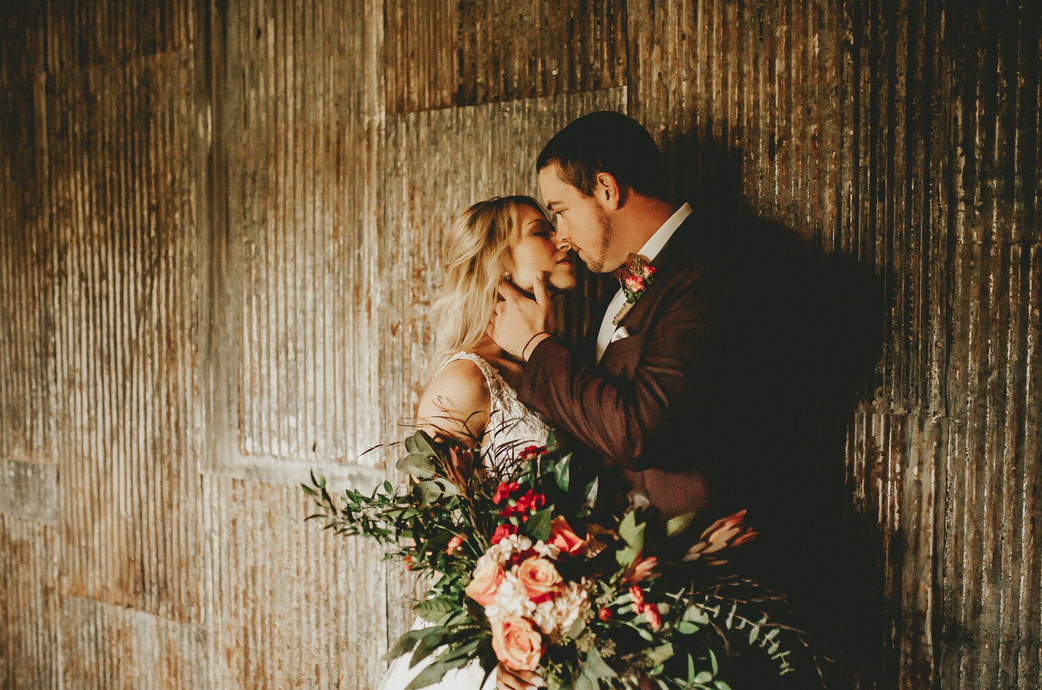 Bride in lace Boho wedding dress with greoom in dark burgundy tux, large bouquet of loose , organic textures with protea and coral roses