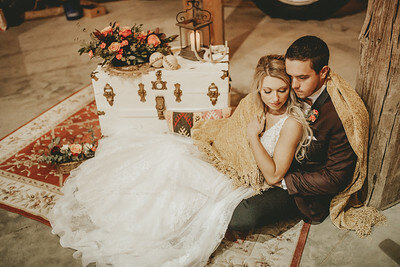 Bride and groom in Iowa barn venue, pose in front of large tractor wheel, with white vintage trunk beside them