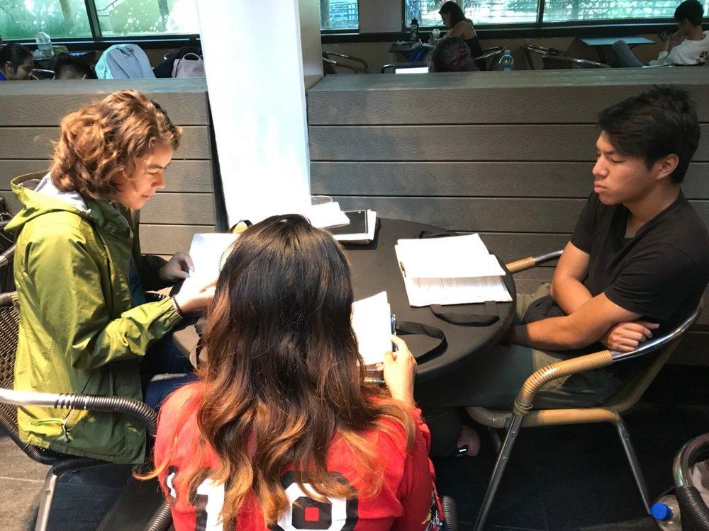 Miyuki Granstrom and Joshua Fujikake studying scripture with a guest.