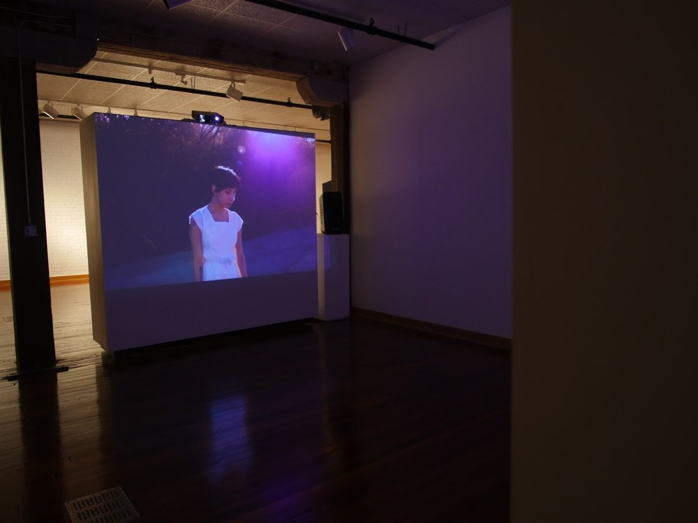 A detail of the two-channel video installation shows El Paso resident Aurore Tarango walking in the dry riverbed of the Rio Grande. Image courtesy of the artists.