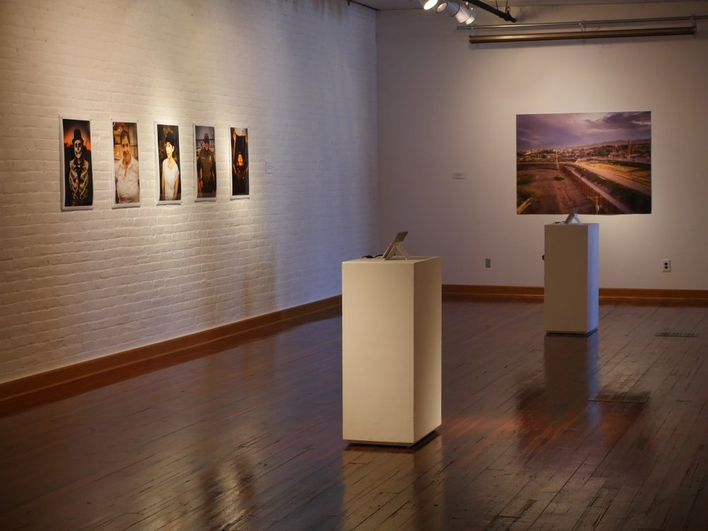 An installation shot of the exhibition shows portraits of El Paso and Juarez locals, a drone shot of the landscape along the fence, and two iPads with videos playing. Image courtesy of the artists.