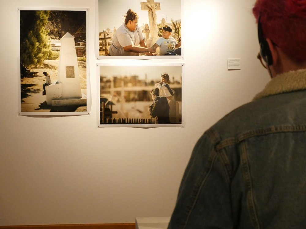 Viewers watch a video about Día de los Muertos in Juarez in front of photographs of families visiting cemeteries. Image courtesy of the artists.