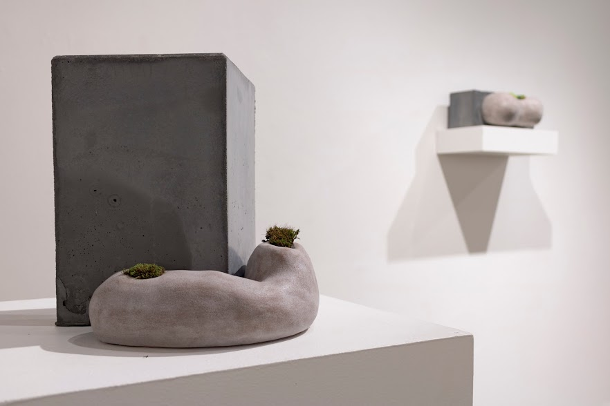 Laura Primozic,  Microenvironments 4 , concrete, earthenware, moss. A low, amorphous figure of earthenware curls around a much taller concrete block, with tufts of moss on either end of the clay shape.Image courtesy of Lucas Stiegman.