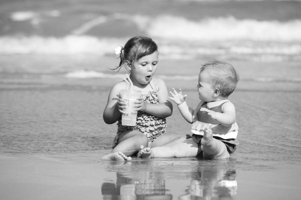 girls-sitting-on-beach-drinking.jpg