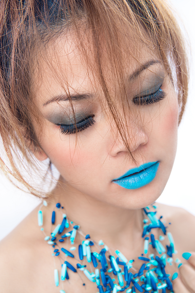 A beauty shot of a woman with blue tone make up