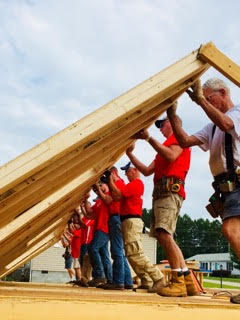 - Itron employee volunteers lift a just completed wall