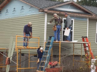 - Habitat's regular volunteer crew siding a new house