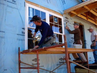 - Habitat volunteers installing energy efficient windows