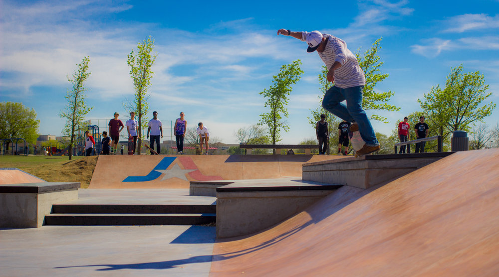 Arlington's Vandergriff Skatepark, with city branding and repurposed benches in the background. Before the park was built, skaters used these benches for tricks.
