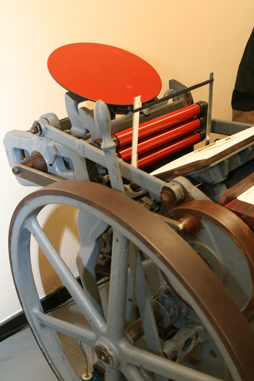 The rollers pick up ink from the platen that turns while the press operates