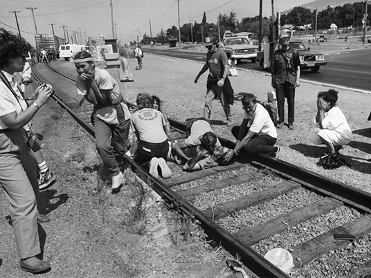 Brian Willson, prone on the tracks leading out of the Concord Naval Weapons Station, Sept. 1, 1987. Brian's autobiography, which includes the story of his sustained protest against arms shipments to Central America, was published in 2011, and titled   Blood on the Tracks:  The Life And Times of S. Brian Willson. photo by  John Skerce