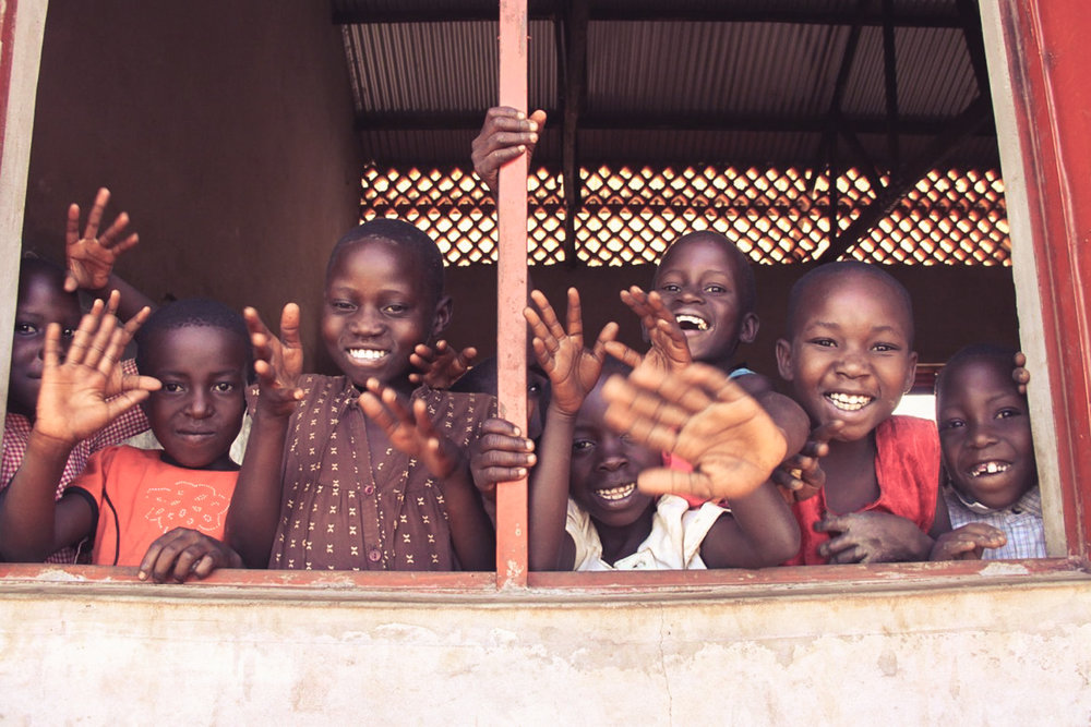 Students of Building Tomorrow Kyambogo Primary School in Uganda wave goodbye to another year as they celebrate the last days of school in 2017. CREDIT: Building Tomorrow