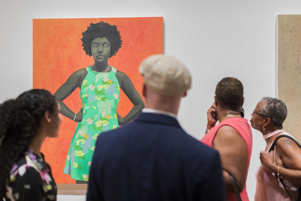 Visitors to The Studio Museum in Harlem examine a painting by Amy Sherald, on view in  Fictions  / Photo: Scott Rudd