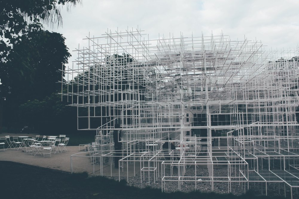 """[The Cloud]  In 2013, the Japanese architect Sou Fujimoto designed a Serpentine Pavilion. Fujimoto sought to create an 'architectural landscape' where people could interact with both, the structure and its surroundings. While the rigid geometry of the structure contrasts with the surrounding greenery, it creates an environment that harmoniously blends nature with human intervention.[5]  """"It is a really fundamental question how architecture is different from nature, or how architecture could be part of nature, or how they could be merged... what are the boundaries between nature and artificial things"""".[6]- Sou Fujimoto"""