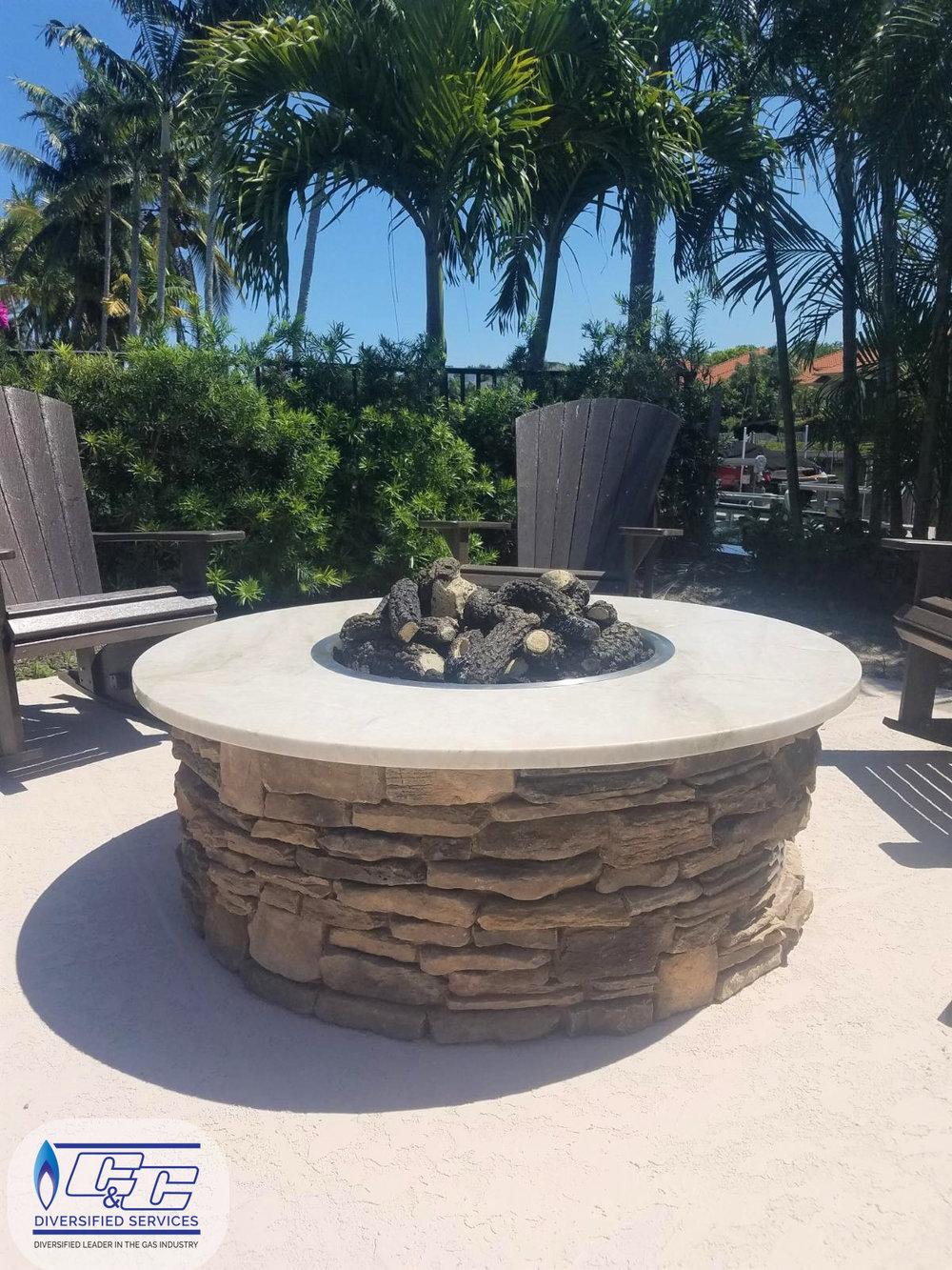 Custom round fire pit - a natural gas manual light fire burner and FireGear Outdoors Split Fire Log Set