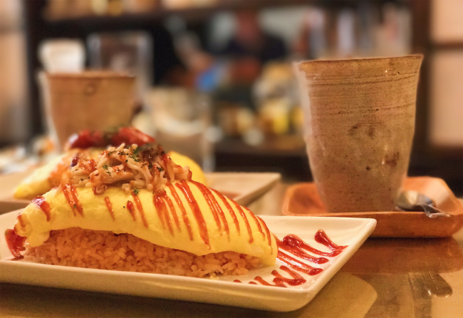 Omurice - A fluffy, gently-cooked egg omelet, resting over tomato bacon rice. Only available 11am-4pmSEE HOW OUR OMURICE IS MADE →