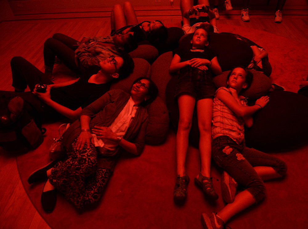 "Museum Goers relax on bean bag chairs while gazing at Christopher Schardt's  Nova , an immersive art installation at No Spectators: The Art of Burning Man   exhibition at Renwick Gallery in Washington, D.C. on July 7, 2018.  The installation is intended to ""bring"" the viewer to the environment of Burning Man with rave music and LED lights."